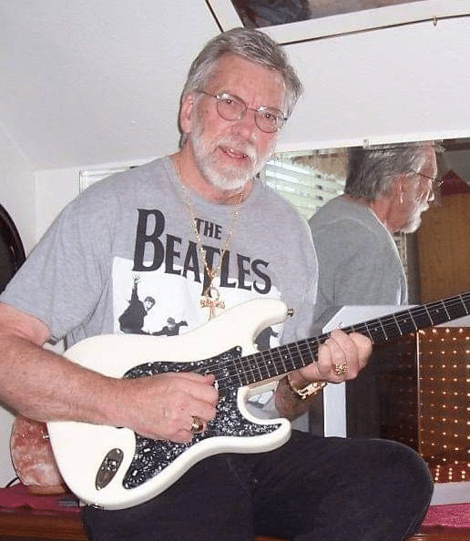 Kelly Don Ford author holding a guitar