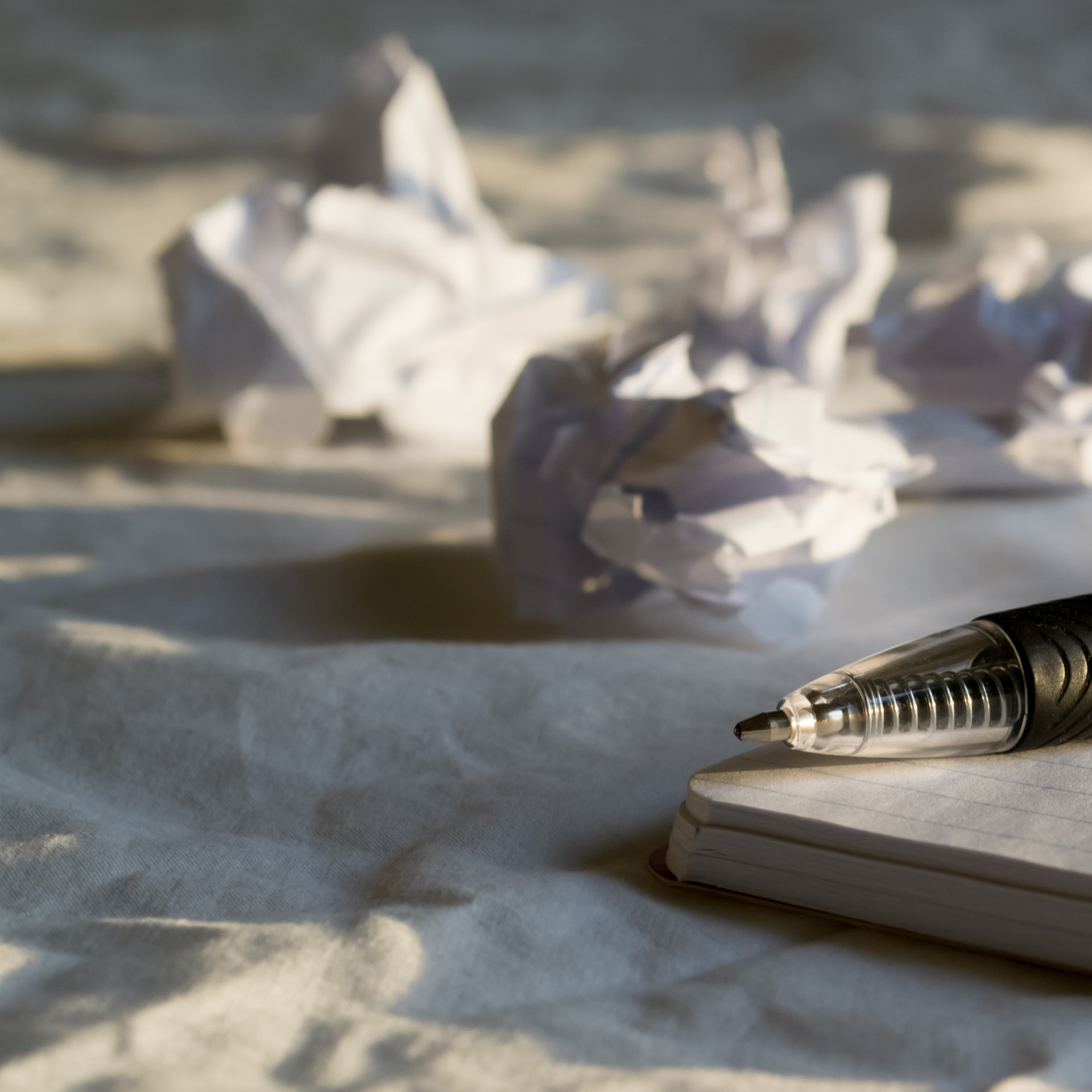 crumpled paper and pen with notebook - How to Overcome Writer's Block - Anne Grove
